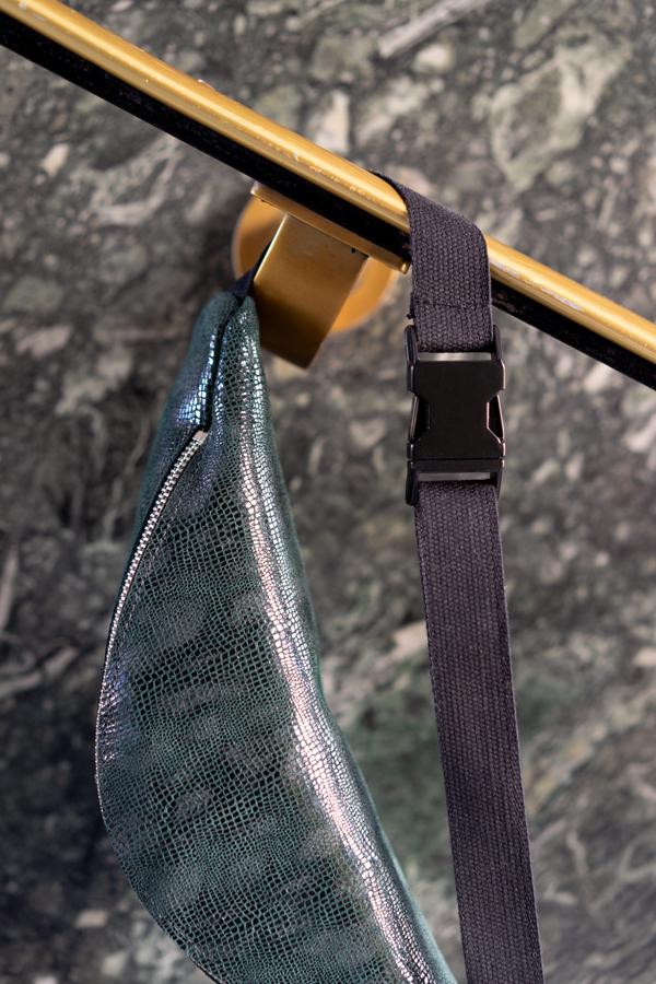 Detail einer dunkelgrünen Bauchtasche mit schwarzer Schnalle und Baumwollband