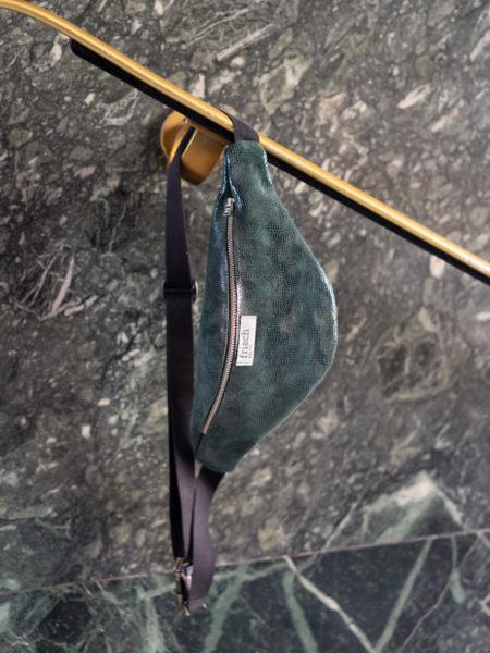 Bauchtasche mit Schlangenprint in dunkelgrün von frisch Beutel hängt an Geländer