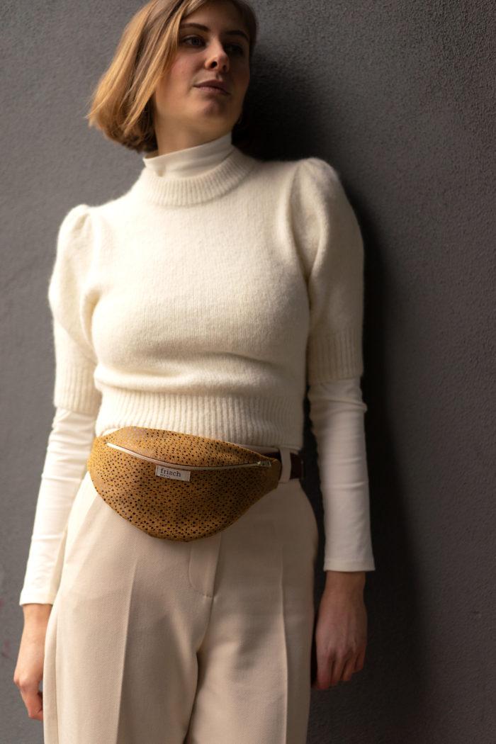 Model trägt helles Outfit mit gelber schicker Bauchtasche um Hüfte