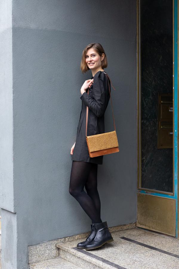 Model trägt senfgelbe Umhängetasche vor Hauseingang