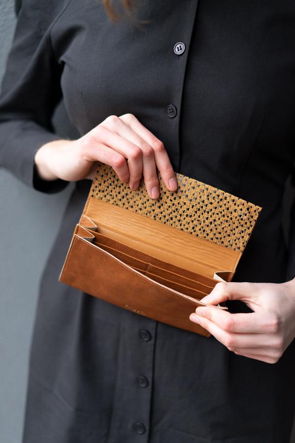 Model zeigt Portemonnaie von Innen mit Kartenfächern aus braunem Leder
