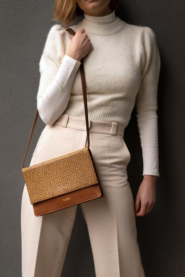 Model präsentiert frisch Handtasche mit Klappe in senfgelb und goldener Prägung