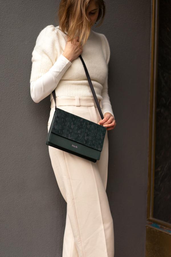 Model zeigt frisch Handtasche mit Klappe aus dunkelgrünem Leder