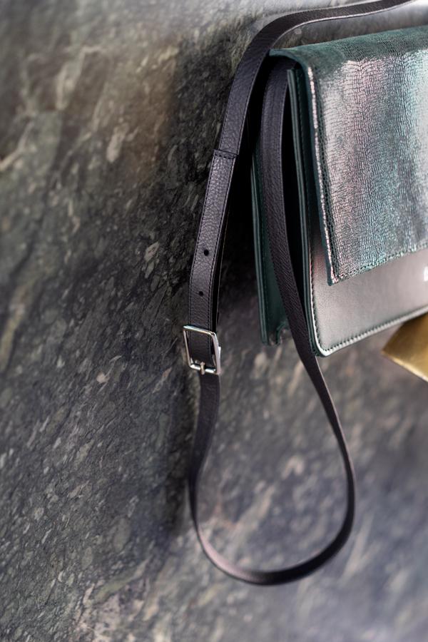 Lederriemen einer Handtasche in schwarz mit silbernen Schnalle zum Verstellen