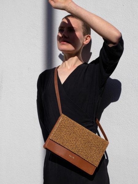 Model trägt schwarzes Kleid und schicke braune Handtasche aus Leder