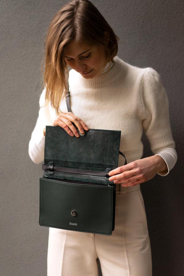 Model schaut in dunkelgrüne Handtasche mit Magnetknopf von frisch Beutel