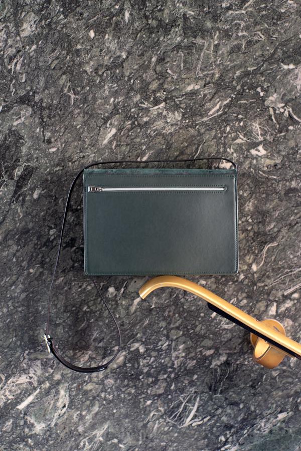 Dunkelgrüne Handtasche von hinten mit Reißverschlussfach vor Marmor Wand