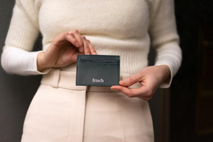 Model zeigt frisch Beutel Kartenetui in dunkelgrün mit silber Prägung