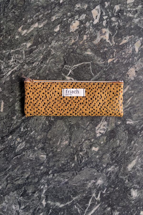 Mäppchen aus gemustertem Leder vor Marmor Wand von frisch Beutel