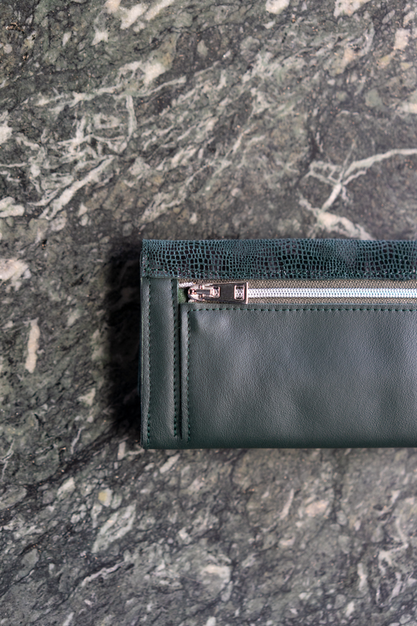 Dunkelgrüner Geldbeutel mit Reißverschluss für Münzen vor Marmor Wand