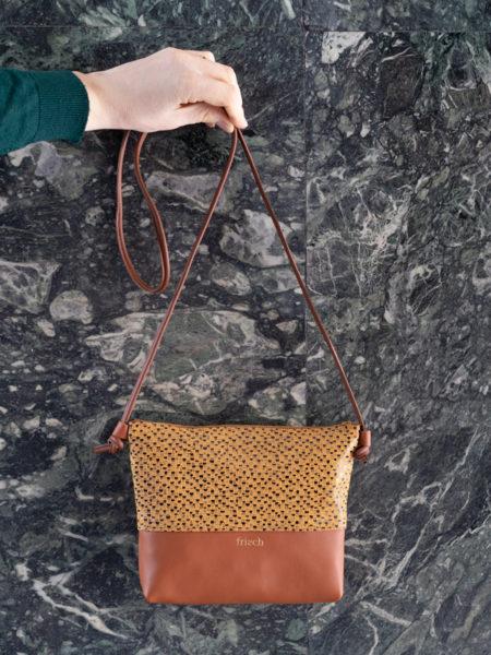 Handtasche Art in braun und senfgelb vor Marmor Wand
