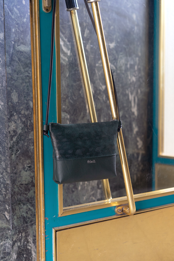 Handtasche in dunkelgrün hängt an Eingangstür in Gold