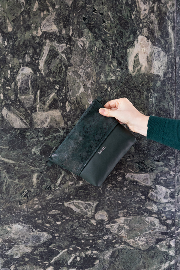 Clutch in dunkelgrün vor Marmor Wand