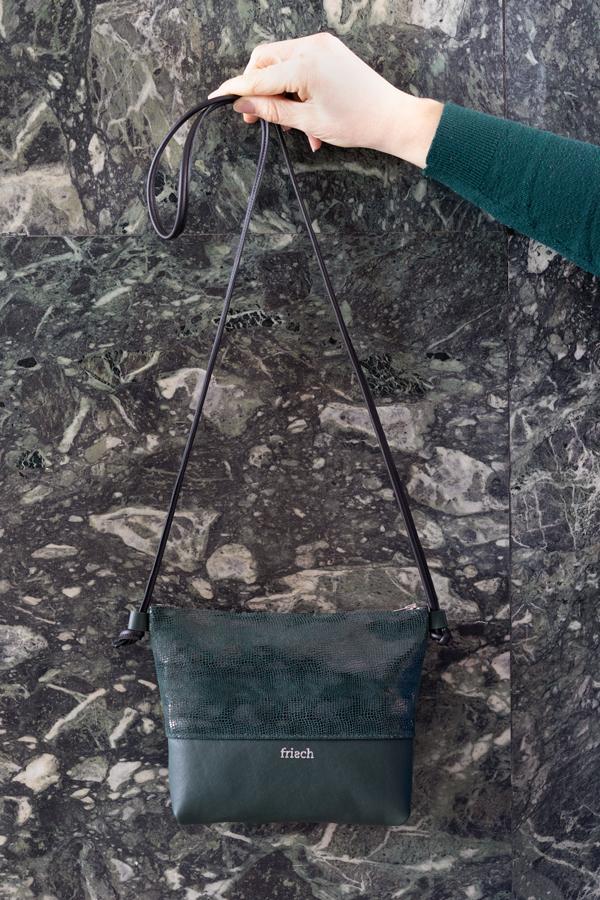 Handtasche mit Schlangenmuster in dunkelgrün vor Mamor Wand