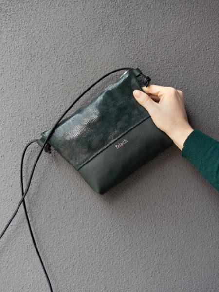 Handtasche in dunkelgrün mit Prägung in Schlangenoptik vor grauer Wand