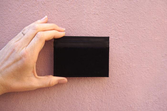 Kartenetui aus Leder in schwarz vor rosa Wand