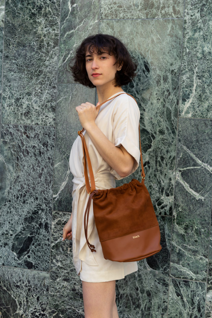 Model trägt frisch Beutel Tasche zum Umhängen aus Leder cognac
