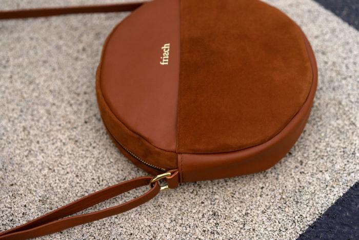 Close up braune Handtasche aus schickem Leder in rund mit goldener Schnalle