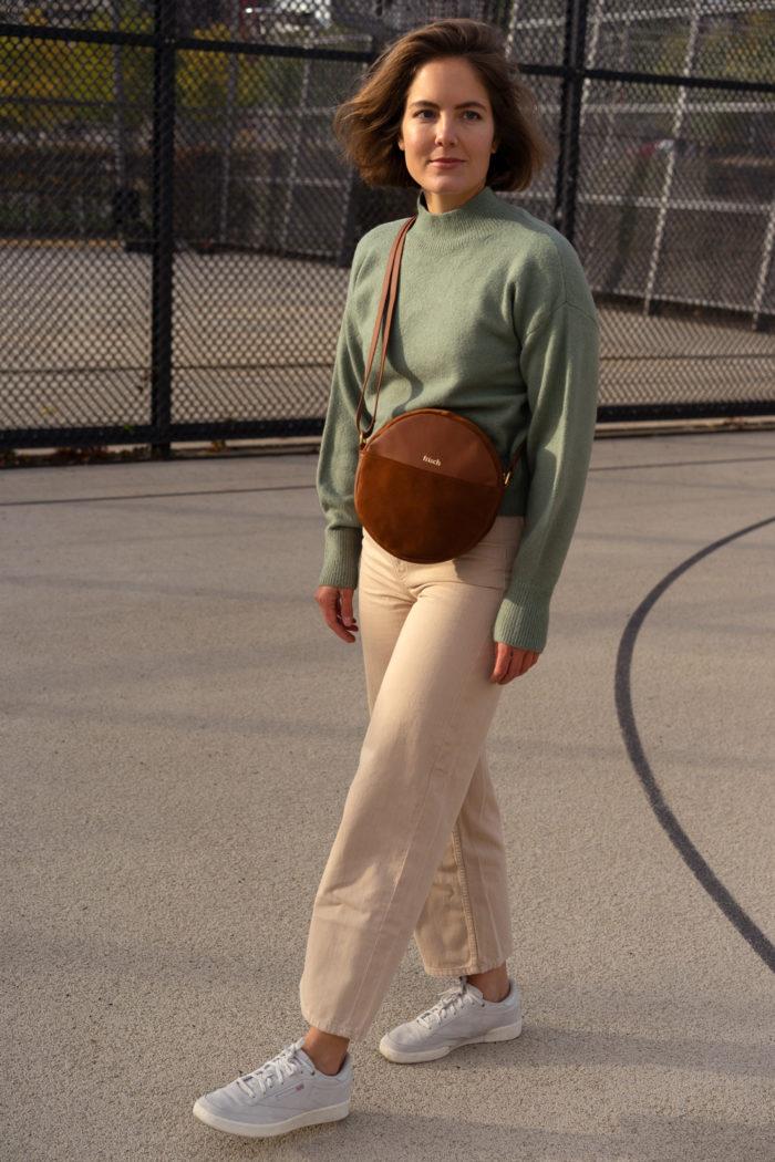 Model trägt schicke braune Umhängetasche auf Sportplatz
