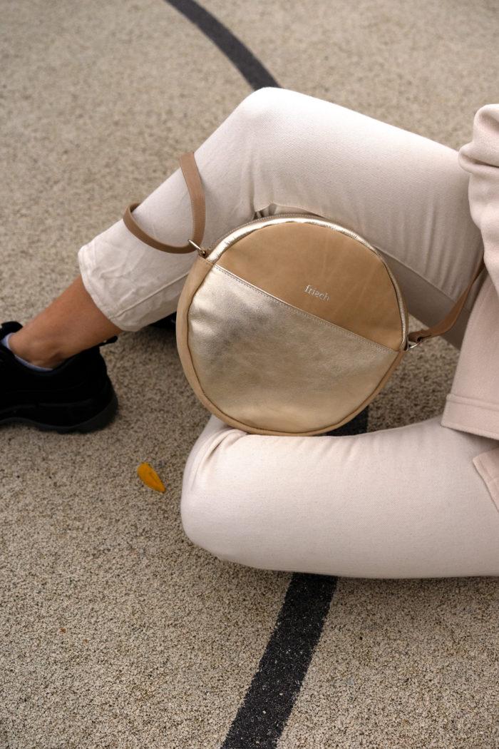 Schicke runde Handtasche in beige und gold auf beigefarbener Hose