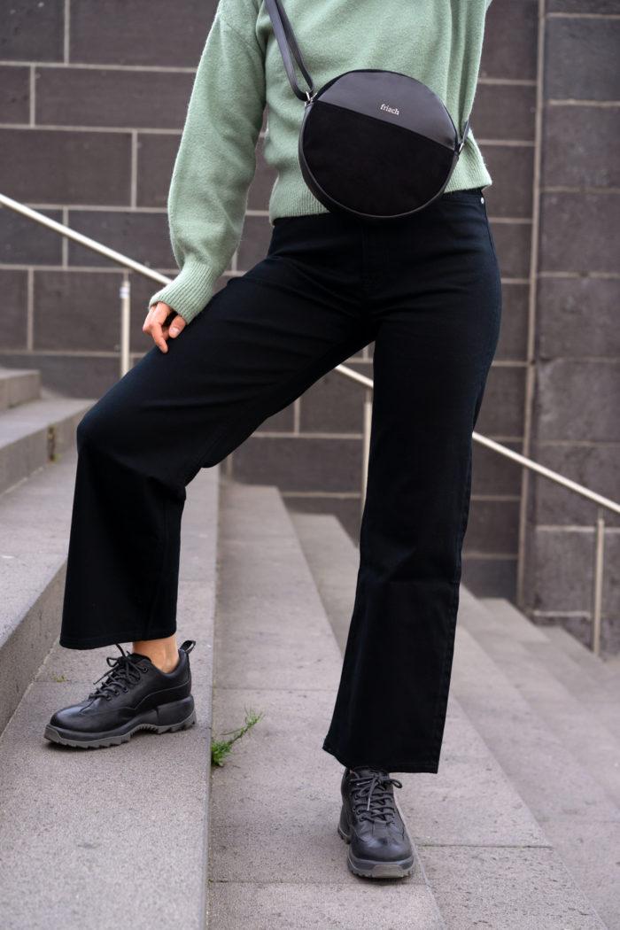 Model trägt schicke runde Handtasche für Damen in schwarz