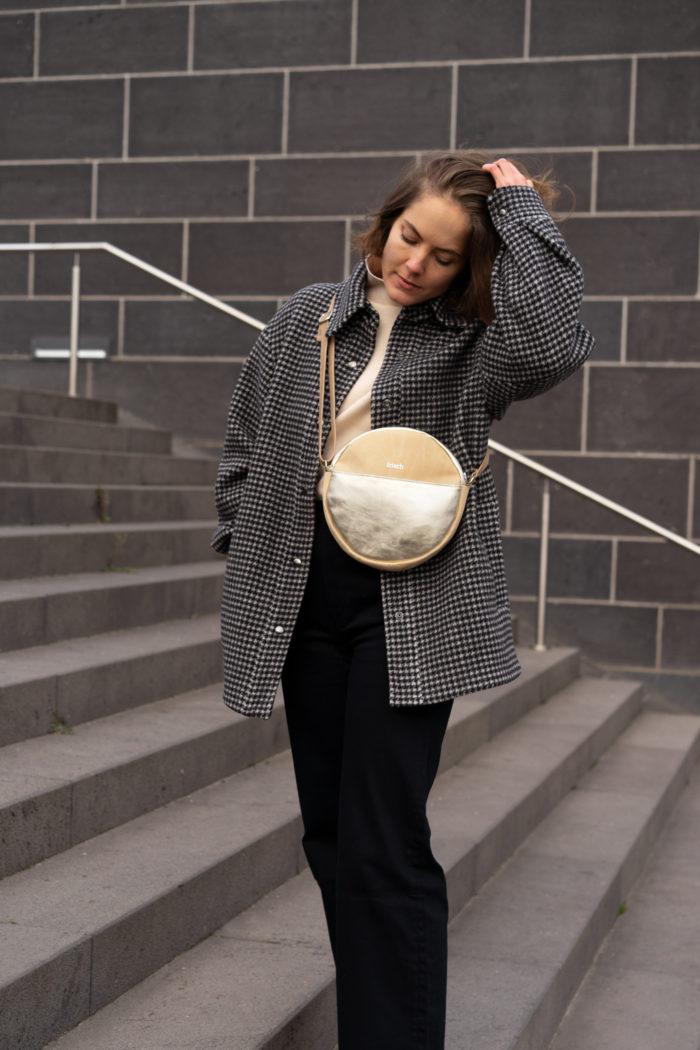 Model mit runder Tasche in beige und gold auf grauer Treppe