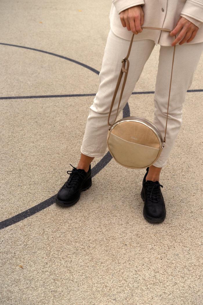 Runde Handtasche in sandfarben und gold von Model gehalten