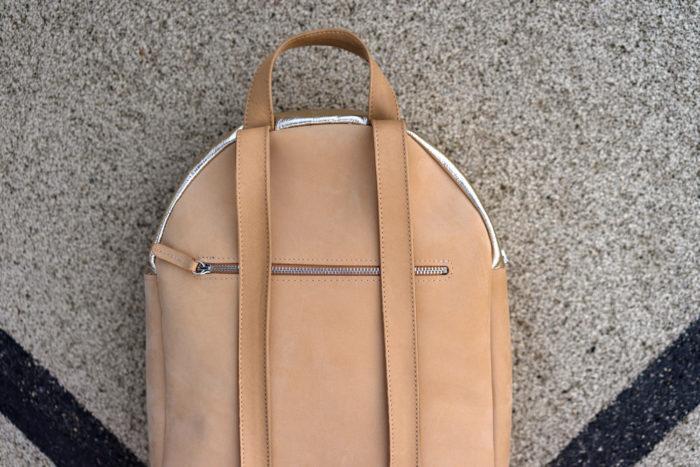 runder Rucksack aus Leder in beige und gold mit Reißverschluss