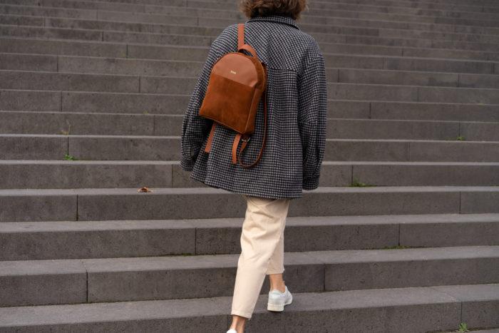 Model läuft auf großer Treppe mit braunem schickem Rucksack