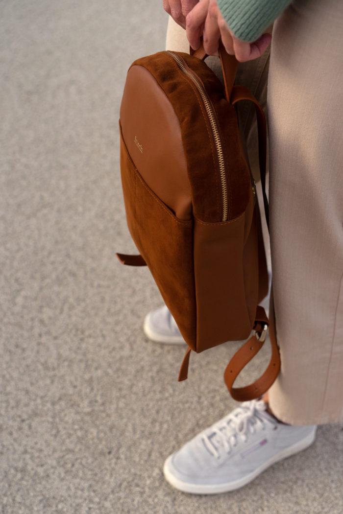 Model mit rundem Rucksack aus braunem Leder und Sneakern