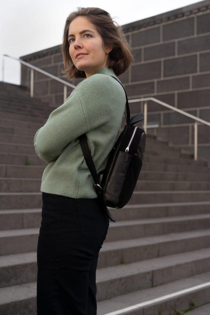Model mit kleinem Rucksack in schwarz und grünem Pullover auf Treppe