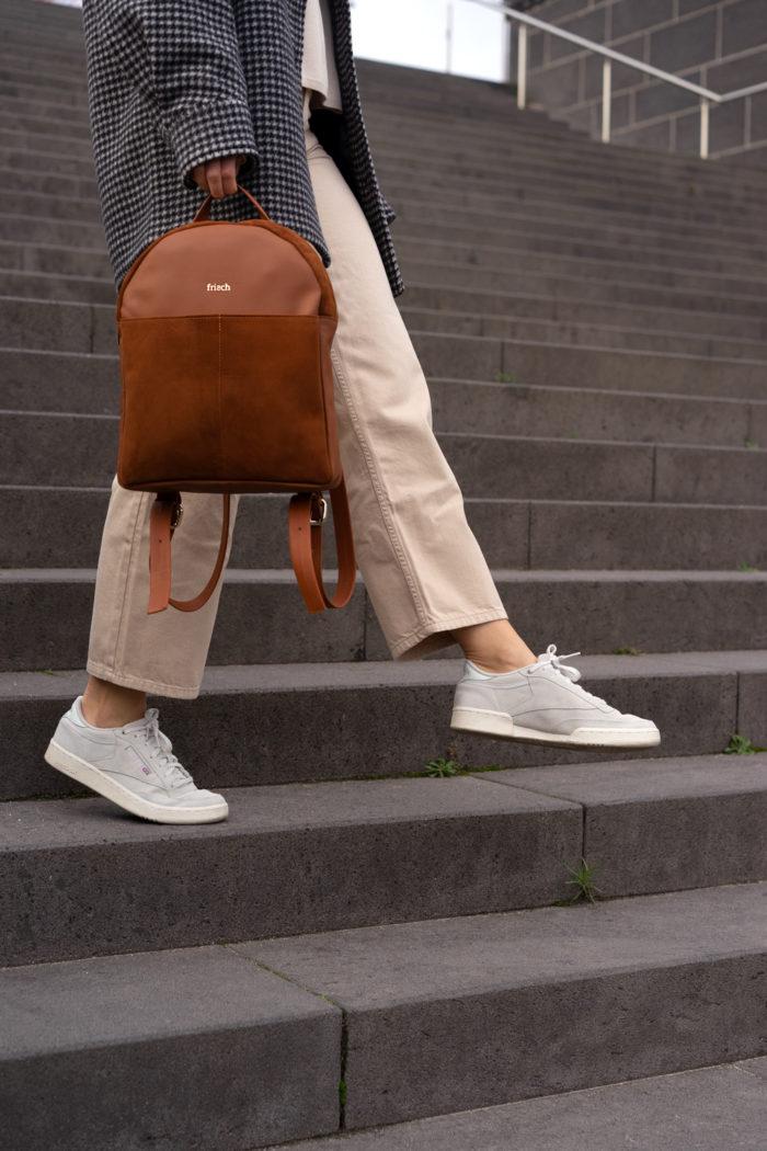 Frau mit schickem braunem Rucksack auf breiter grauer Treppe