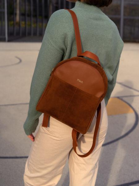 Model auf Sportplatz mit schickem Rucksack in braun und grünem Pullover