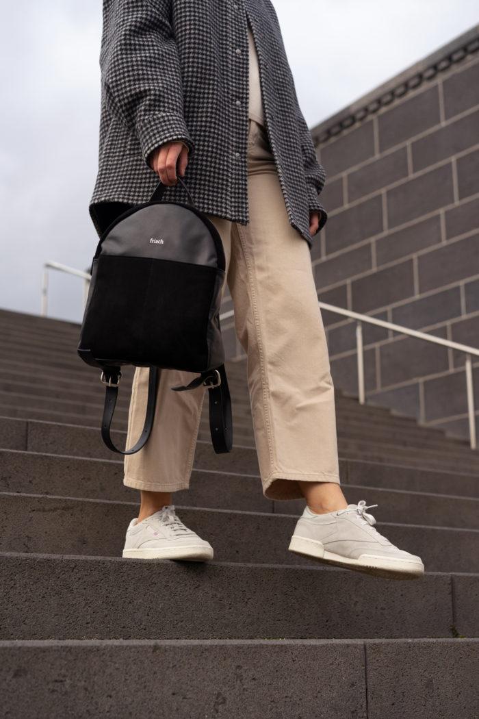 Model mit schwarzem Rucksack und Turnschuhen auf grauer Treppe
