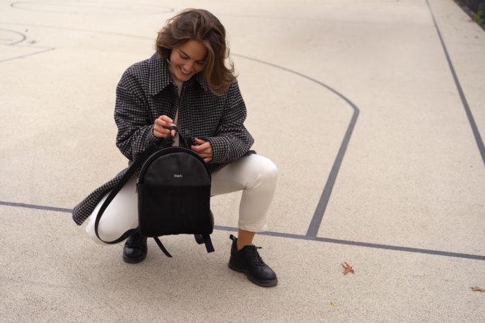 Modell mit modischem Rucksack in schwarz auf Sportplatz