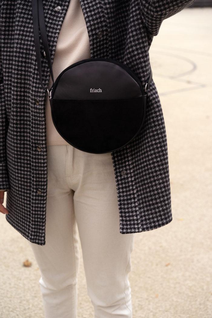 Runde Tasche aus schwarzem Leder auf Karojacke