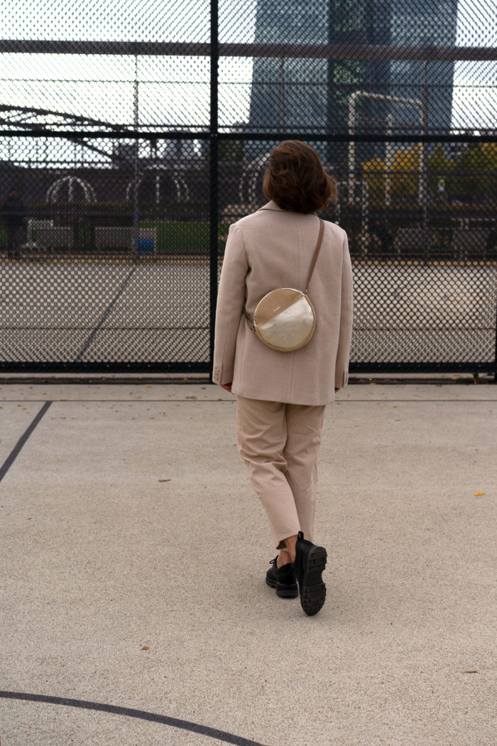 Model auf Sportplatz mit runder Handtasche in beige und gold