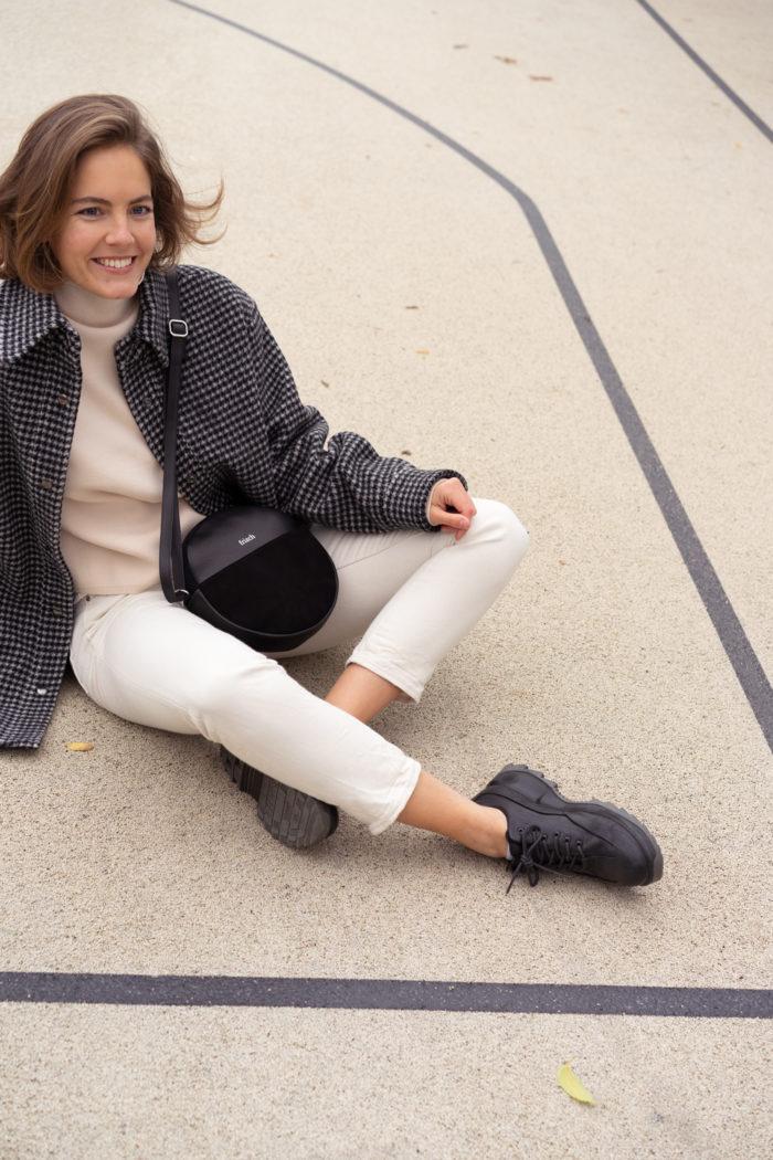 Model auf Sportplatz sitzend mit runder Handtasche aus Leder in schwarz