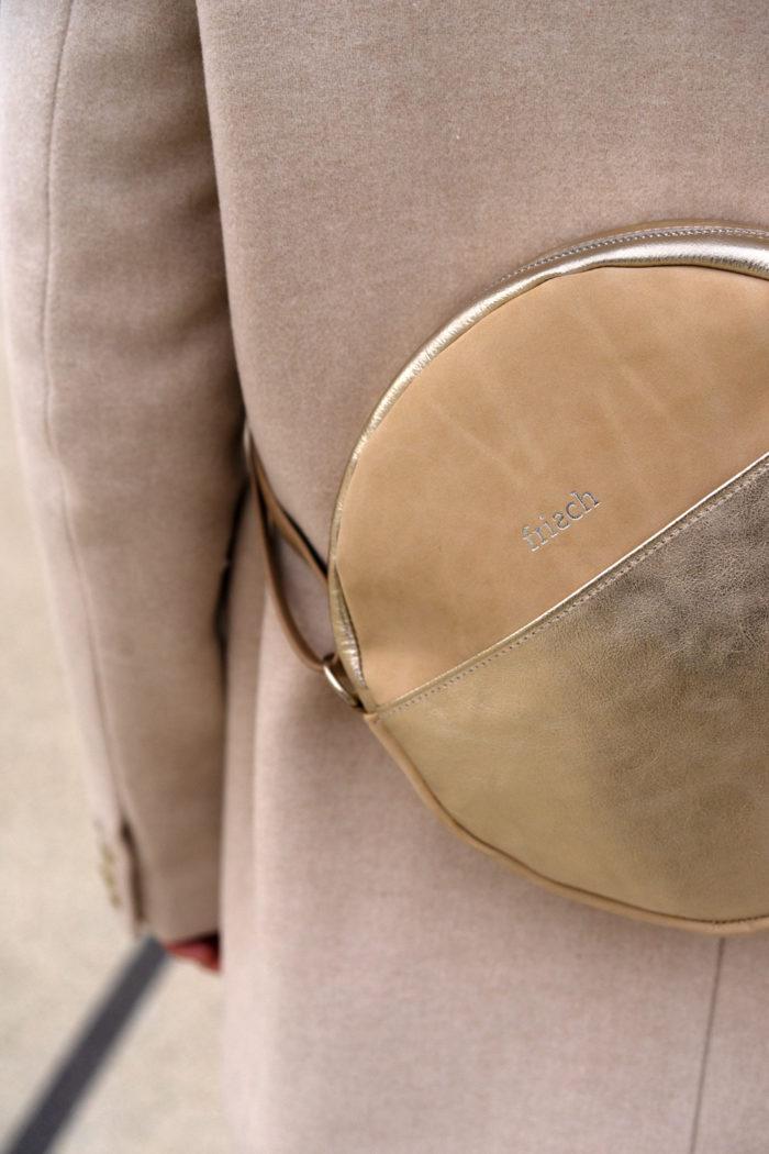 Close up einer runden Handtasche in sandfarben und gold