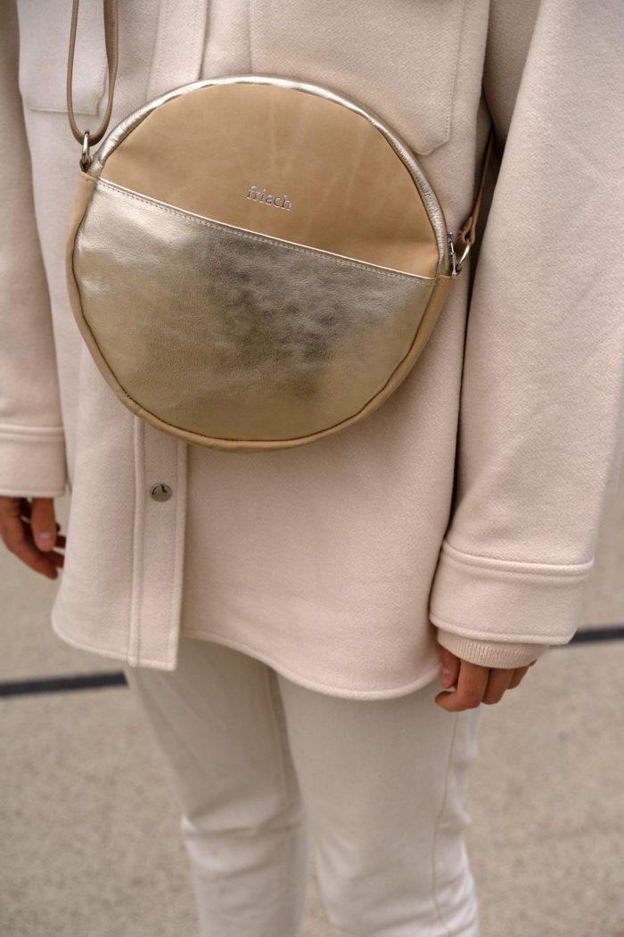 runde Handtasche mit gold an Model mit hellem Outfit