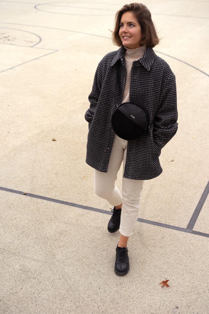Model auf Sportplatz mit runder Handtasche aus Leder in schwarz