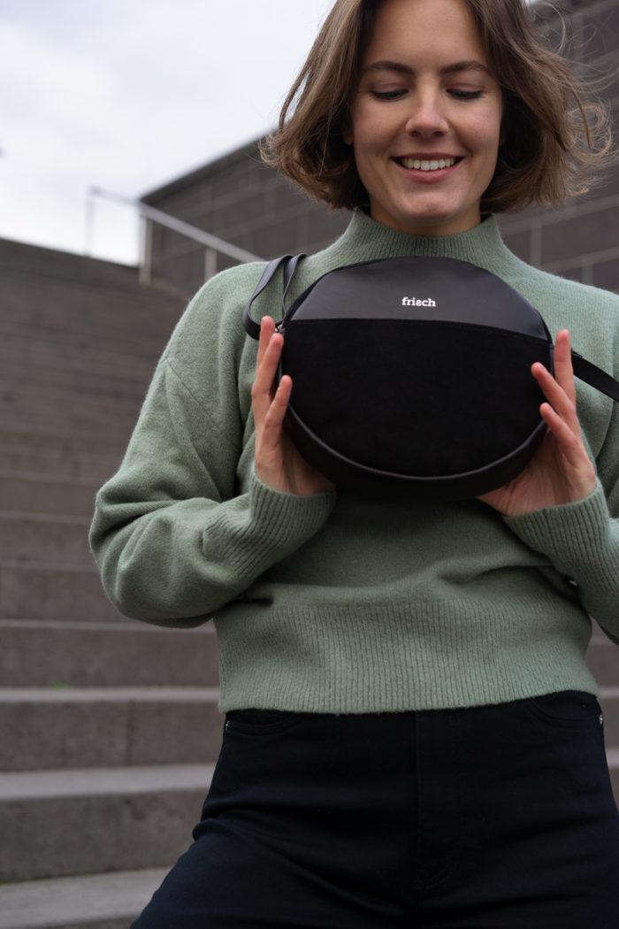 Model präsentiert schicke runde Handtasche in schwarz mit Logo