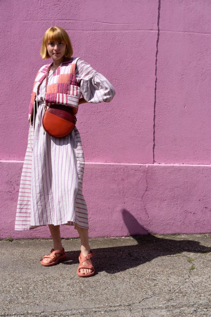 Modell mit veganer Handtasche vor pinkfarbener Betonwand