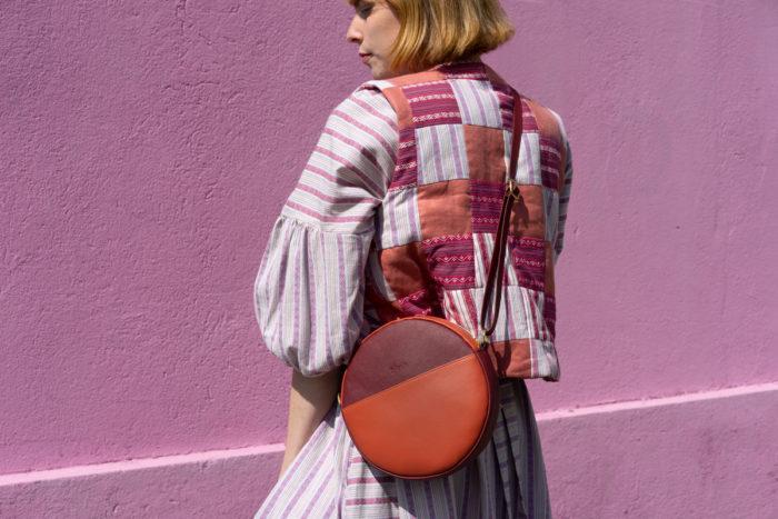 Modell im Anschnitt mit Handtasche aus Apfelleder