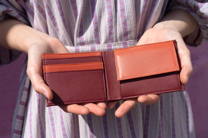 Brieftasche aus Apfelleder in Händen vom Modell in bordeauxrot und orange