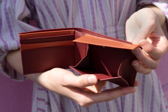 Brieftasche aus Apfelleder in Händen vom Modell in bordeauxrot und orange geöffnet