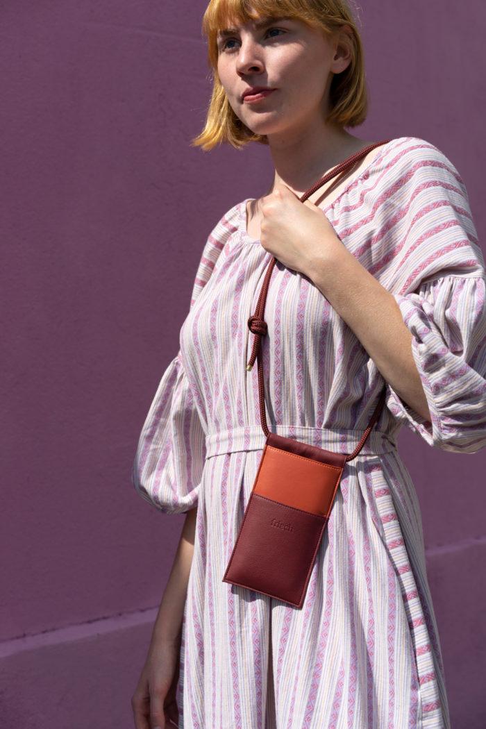 Produktbild einer veganen Handtasche in orange und bordeauxrot gezeigt an Modell
