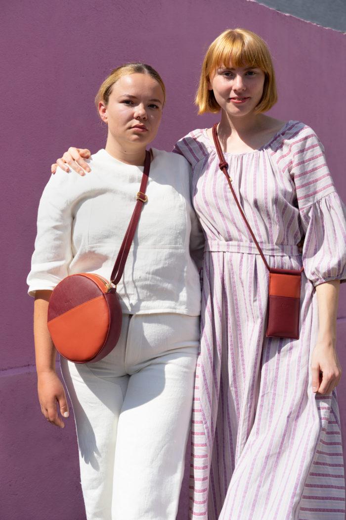 Modelle mit einer veganen Handytasche in orange und bordeauxrot und Runden Tasche