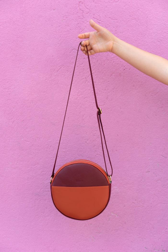 Runde Tasche Apfel vor pinkfarbener Wand