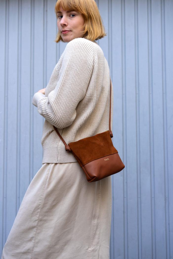 Modell trägt Handtasche Erde aus braunem Glatt- und Veloursleder